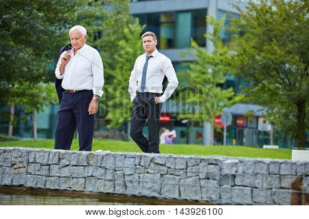 Two businessmen walking together outside the office in the city
