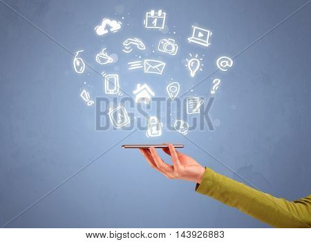 An elegant caucasian white hand holding mobile phone with drawn social media icons in front of an empty clear blue background concept