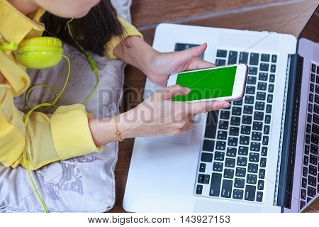 Woman's Hands Using Cell Phone And Laptop Computer On Floor Wooden At Home.