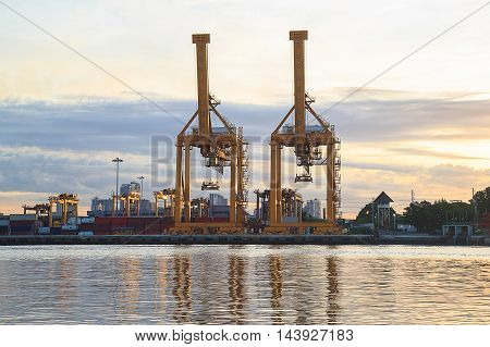 Working crane loading bridge in shipyard at sunrise time for Logistic Import Export background