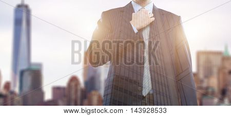 Double exposure of a businessman adjusting his necktie in front of a big city