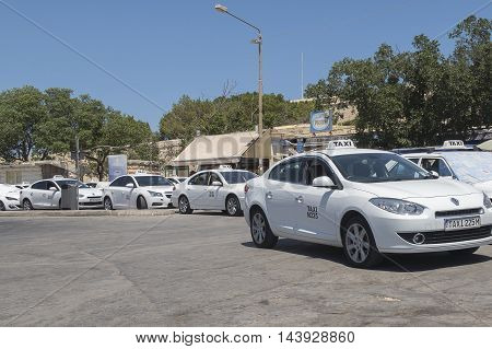 VALLETTA, MALTA 02 AUGUST 2016: Taxis at a stand before Valletta City Gate. White taxis can pick up passengers waving hand on the road, except bus-stops.
