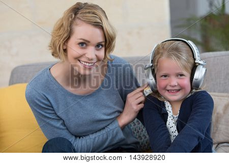 happy mom and daughter listening music at home