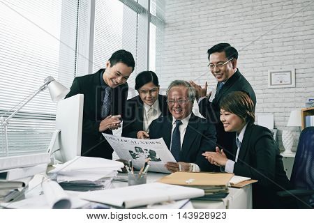 Happy team of lawyers reading article in newspaper