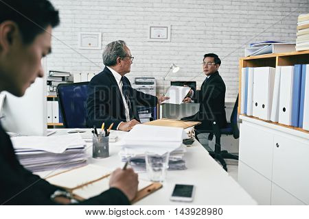 Attorney giving important document to his coworker