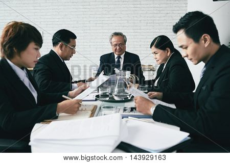 Team on lawyers reading documents at big table