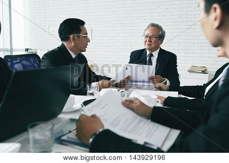 Team of Asian prosecutors discussing case at table