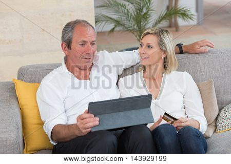 happy senior couple buying on internet at home