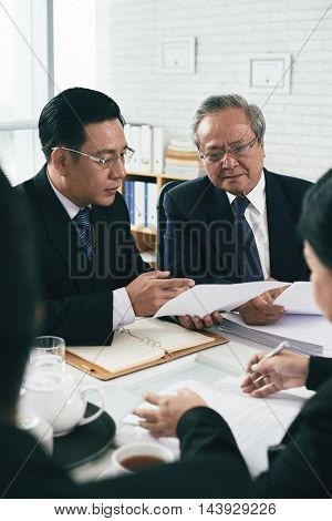 Mature Vietnamese lawyer consulting his younger colleague