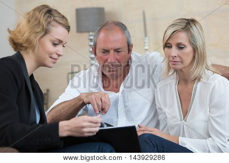 senior couple negociating with businesswoman for new investment