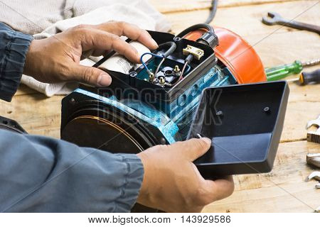 Electric motor  and man working equipment repair on wooden floor background.Background mechanic or equipment. Zoom in