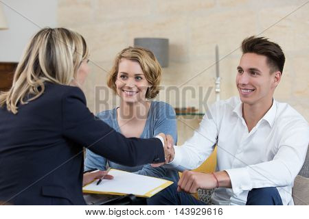 young couple signing financial contract in house