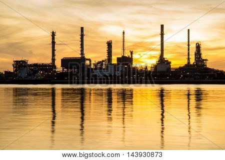 Oil refinery factory in silhouette and sunrise sky