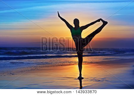 Black silhouette of woman stretching at yoga retreat on sunset sand beach colourful sky ocean surf background. Lifestyles people outdoor activity sport on family summer vacation on tropical island