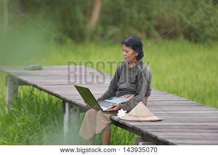 Grandmother play computer to talk to children in different provinces.