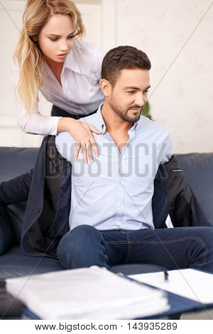 Young blonde secretary touch young businessman in office while take off suit