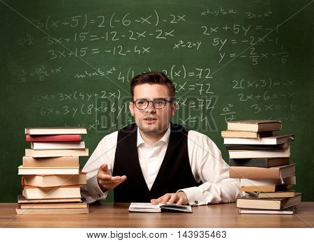 A young ambitious teacher in glasses sitting at classroom desk with pile of books in front of blackboard full of math calculations, numbers, back to school concept.