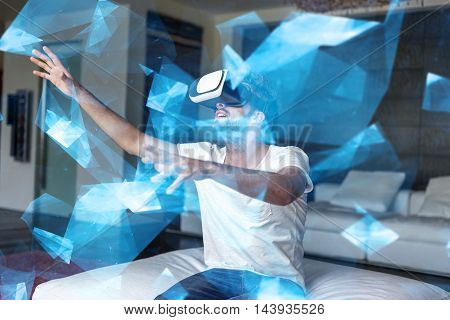 Casual caucasian man playing with VR headset in blue glowing polygon world