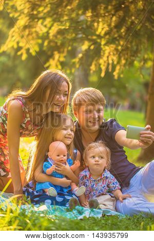 Happy family taking selfie sitting on the grass in a city park.
