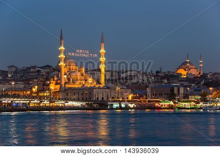 ISTANBUL TURKEY - JUNE 20 2015: Night view on Galata Bridge the Suleymaniye Mosque and New Mosque in Eminonu Istanbul Turkey