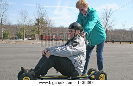 Senior Woman Giving Boost To Senior Man On Skateboard!