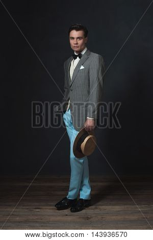 Man In Retro 1920S Fashion Holding Straw Hat.