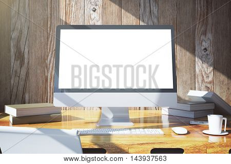 Front view of creative designer desktop with blank white pc monitor keyboard coffee cup book and other items on wooden wall background. Mock up 3D Rendering