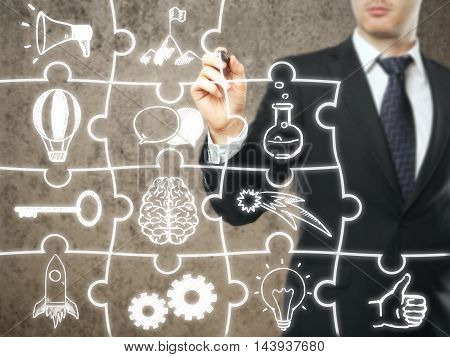 Businessman drawing business icons on abstract puzzle pieces