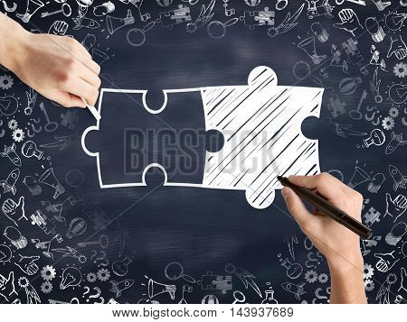 Male hands drawing puzzle pieces and success icons sketch on blackboard background. Business partnership sketch