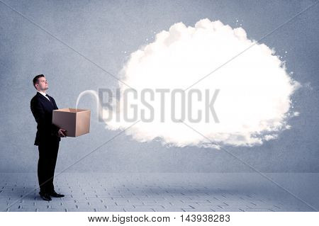 A young cheerful business person holding a cardboard box with illustration of white empty cloud concept.