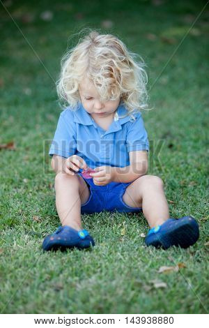 Beautiful boy three year old with long blond hair sitting on the grass