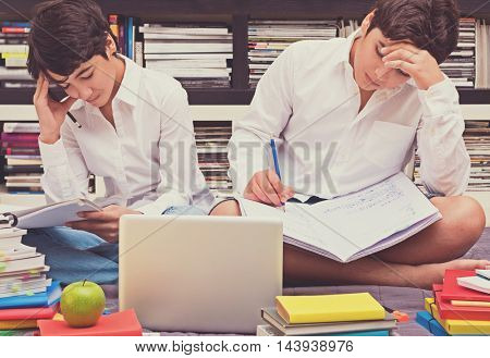 Two schoolboys sitting in the library and thinking about a difficult task, doing home work, education in the high school, back to school