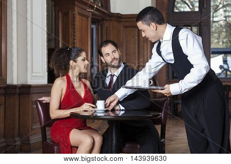 Young Waiter Serving Coffee To Tango Couple In Restaurant