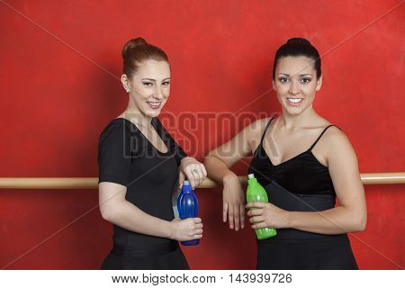 Female Friends Holding Water Bottles In Ballet Studio