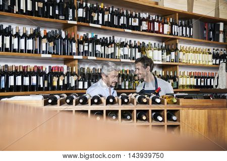 Salesman Assisting Customer In Buying Wine In Supermarket