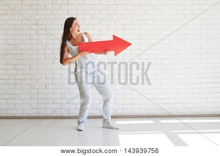 Smiling pretty brunette is standing and holding big red arrow and looking away, white brick wall in background