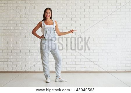 Smiling beautiful woman standing and points finger towards, white brick wall on background
