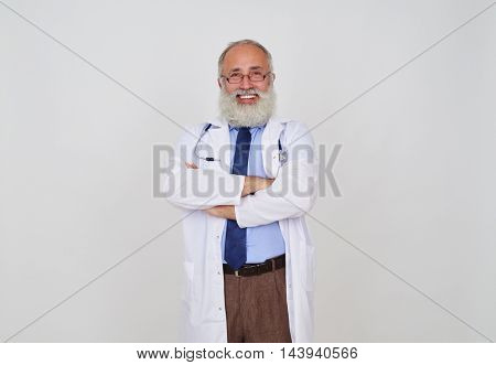 A portrait of delighted senior bearded doctor with crossed hands, against white background, wearing glasses and with a stethoscope on his neck