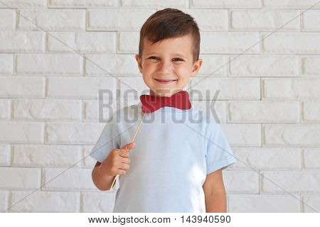 Adorable small boy holding a paper bow tie on stick and smiling while standing against white wall