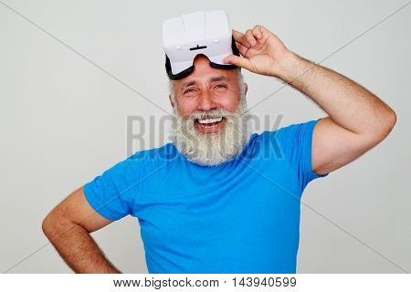 Aged bearded man is smiling satisfied by work of virtual reality headset technology isolated against white background