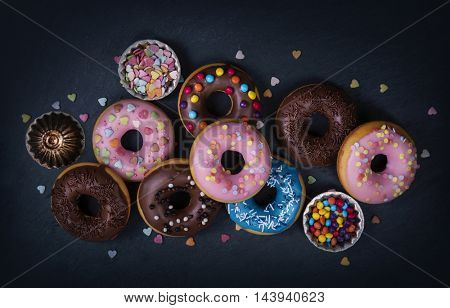 Donuts on a black slate surface