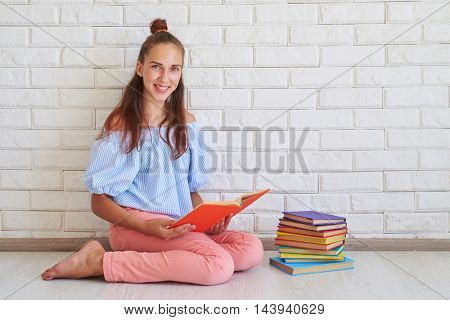 A delighted young girl is sitting on the floor near the pile of books while posing at the camera
