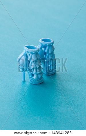 Blue high heeled doll shoes on blue background