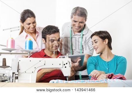 Tailors Using Tablet Computer In Sewing Factory