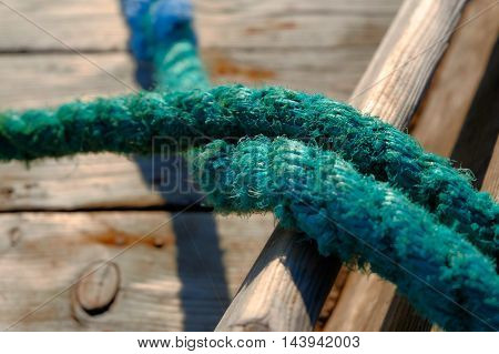 Close up on rope of green color of fishing boat.