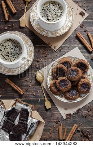 A plate of chocolate homemade cookies and two cups of coffee
