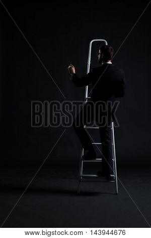 Businessman writing imaginary text on stairs over black background. Business and office concept.