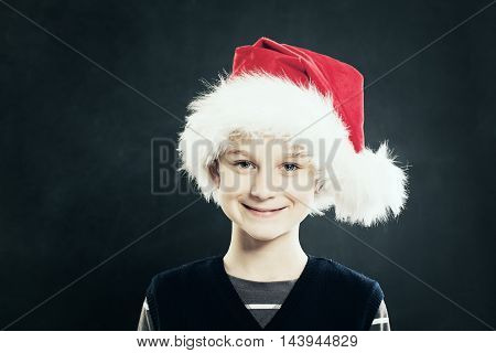 Christmas. Smiling Child in Red Santa Hat