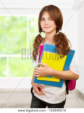 Pretty girl standing in the classroom with colorful textbooks in hands, studying with pleasure, back to school