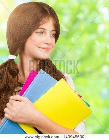 Closeup portrait of a nice schoolgirl with colorful textbooks in the park, going to school, enjoying education, back to school in september